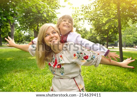 Portrait of happy Ukrainian mother and son in summer park, outdoor - stock photo