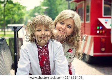 Portrait of happy Ukrainian mother and son in summer park, outdoor, toned - stock photo