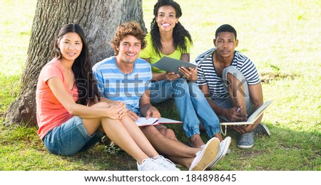 Portrait of happy university students studying together on college campus - stock photo