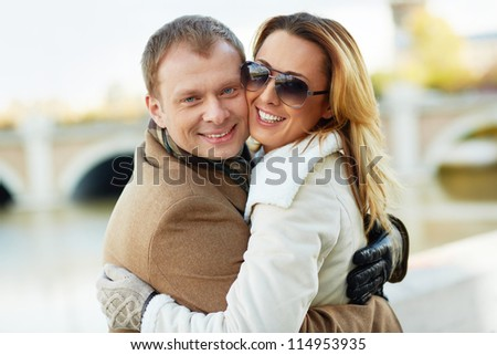 Portrait of happy urban couple in embrace looking at camera outdoors - stock photo