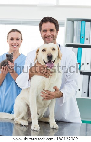 Portrait of happy veterinarians with dog and kitten in hospital