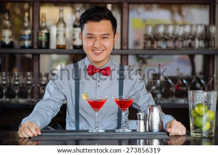 Portrait of happy Vietnamese barman standing at the counter - stock photo