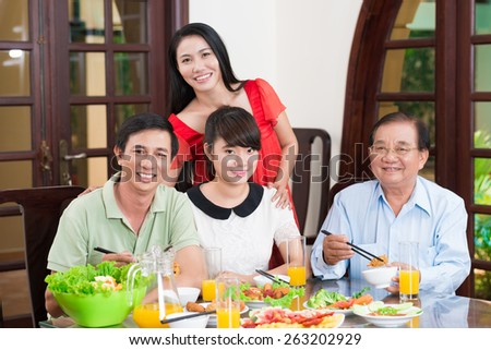 Portrait of happy Vietnamese family at the dinner table - stock photo