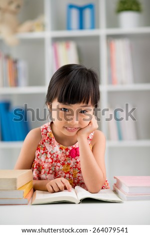 Portrait of happy Vietnamese girl reading book at a nursery
