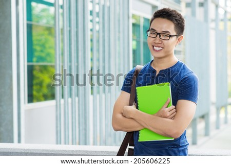 Portrait of happy Vietnamese student with a textbook - stock photo