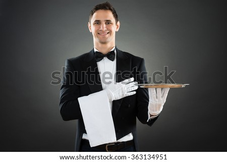 Portrait of happy waiter with empty tray and towel standing against gray background - stock photo