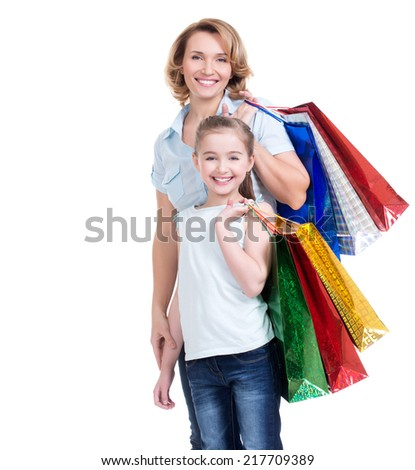 Portrait of happy  white mother and young daughter with shopping bags- isolated. Happy family people concept. - stock photo