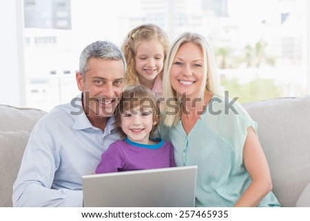 Portrait of happy with laptop at home - stock photo