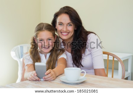 Portrait of happy woman and daughter holding mobile phone at table in house - stock photo