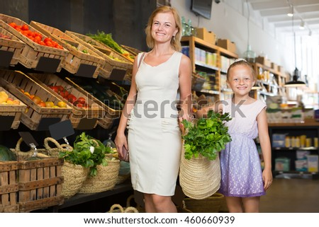 Portrait of happy woman and girl buying fresh greens in grocery shop - stock photo