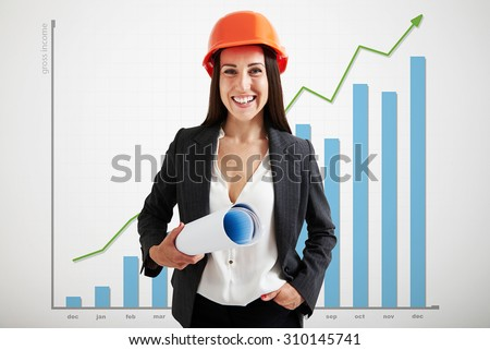 portrait of happy woman architect in orange hardhat holding plan and looking at camera over graph with positive dynamics  - stock photo