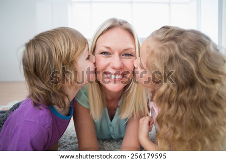 Portrait of happy woman being kissed by children at home - stock photo