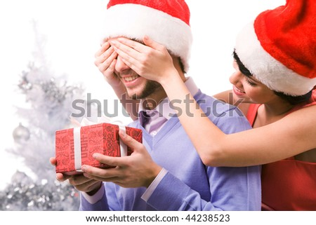 Portrait of happy woman closing male?s eyes by her hands while he holding giftbox - stock photo