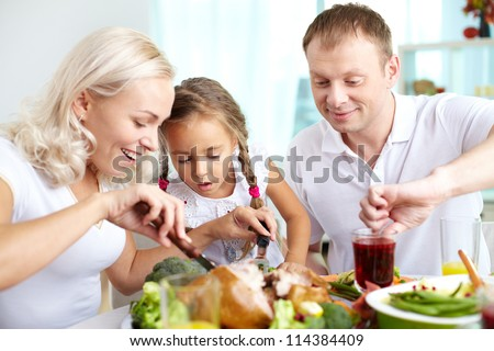 Portrait of happy woman cutting turkey at festive table with her husband and daughter near by - stock photo