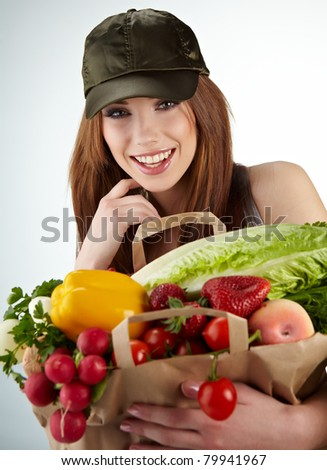 Portrait of happy woman holding a shopping bag full of groceries on white background