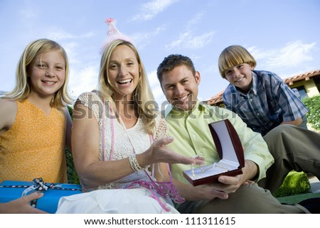 Portrait of happy woman holding gift while sitting with family against clear sky - stock photo