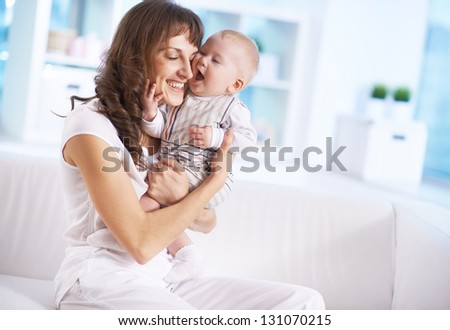 Portrait of happy woman holding her small son and expressing affection - stock photo