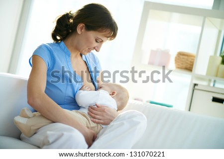 Portrait of happy woman holding her small son and feeding him - stock photo