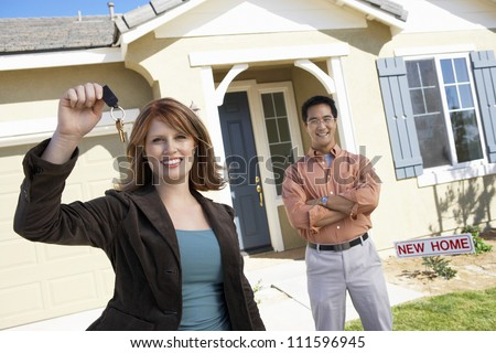 Portrait of happy woman holding keys of new home with man standing in background - stock photo