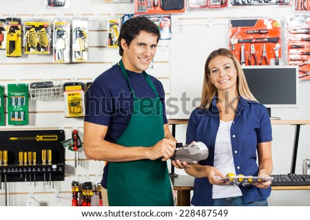 Portrait of happy woman holding screwdriver set with worker swiping credit card at hardware store - stock photo