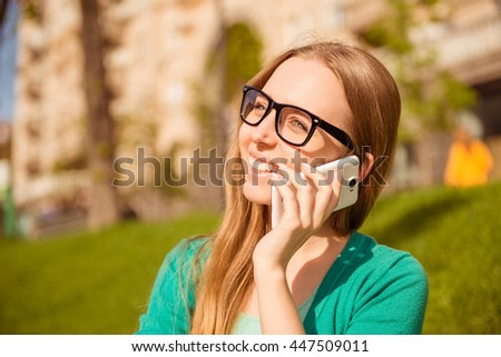 Portrait of happy woman in glasses talking on phone in park