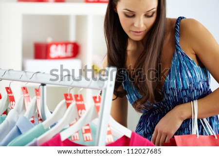 Portrait of happy woman looking at her paperbags in clothing department - stock photo