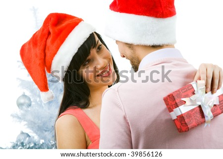 Portrait of happy woman looking at man with smile and keeping giftbox behind his back - stock photo