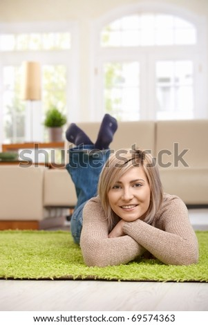 Portrait of happy woman resting on floor at home, looking at camera, smiling. ? - stock photo