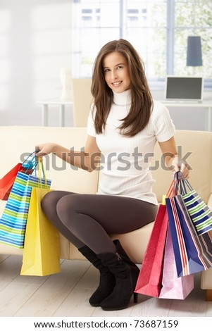 Portrait of happy woman sitting on sofa at home holding shopping bags, smiling.? - stock photo