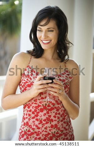 Portrait of happy woman standing and holding a glass of red wine. Vertical shot.
