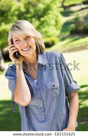 Portrait of happy woman using cell phone in park - stock photo