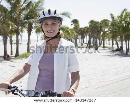 Portrait of happy woman wearing helmet riding bicycle on tropical beach - stock photo