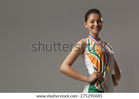 Portrait of happy woman wearing medal with hands on hip isolated over gray background - stock photo