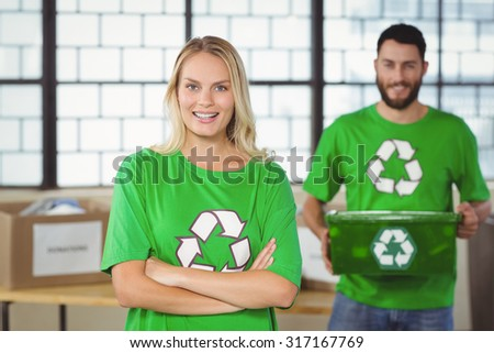 Portrait of happy woman with arms crossed standing with colleague in creative ofice