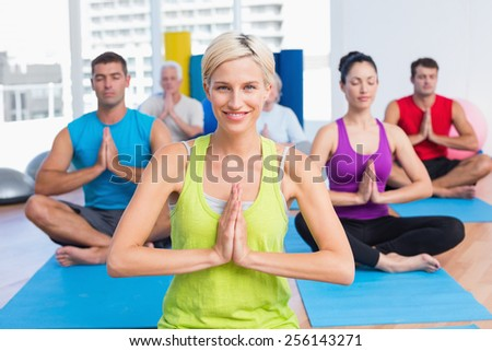 Portrait of happy woman with class meditating in fitness studio - stock photo