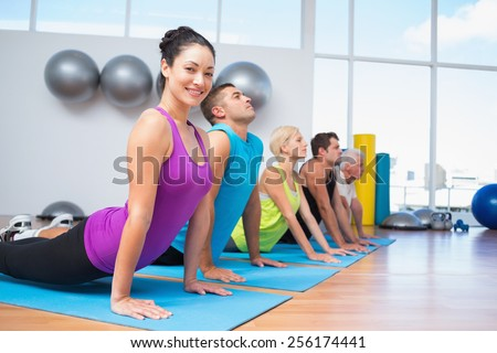 Portrait of happy woman with friends doing the cobra pose in fitness studio