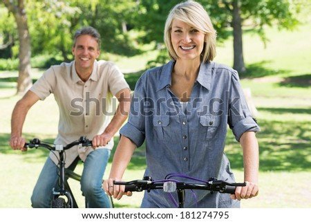 Portrait of happy woman with man riding bicycles in park