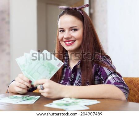 Portrait of happy woman with many euro in home
