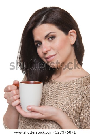 Portrait of happy woman with mug in hands looking at camera, white background