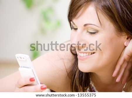 portrait of happy woman with white phone (focus on smile) - stock photo
