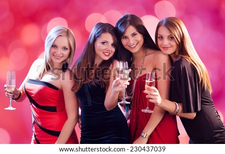 Portrait of happy women holding champagne flutes at nightclub - stock photo