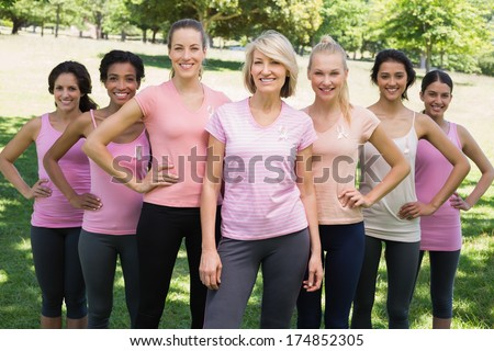 Portrait of happy women participating in breast cancer awareness at park - stock photo