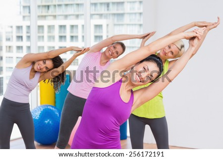 Portrait of happy women practicing stretching exercise in gym
