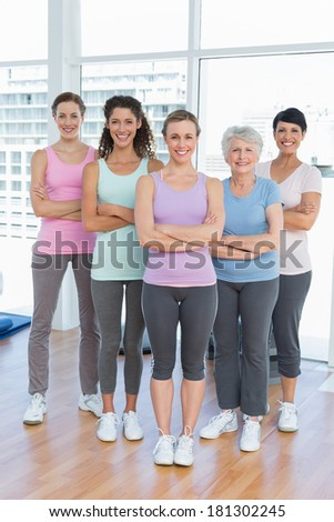 Portrait of happy women with arms crossed standing in the yoga class - stock photo