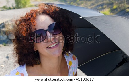 Portrait of happy women with umbrella on summer day.