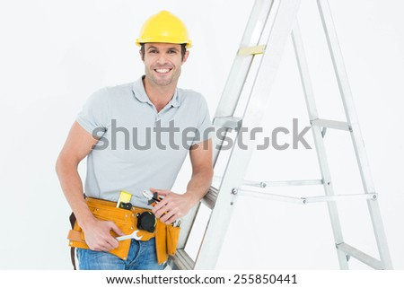 Portrait of happy worker holding tools while leaning on step ladder