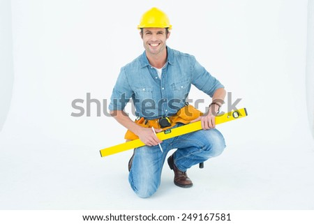 Portrait of happy worker using spirit level while kneeling over white background - stock photo