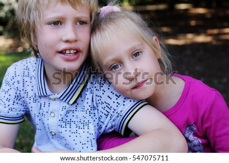 Portrait of happy 5 years old girl with her autistic 8 years old brother outdoors