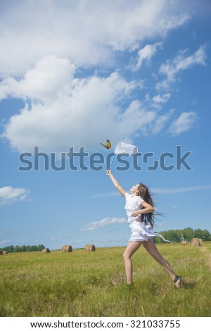 Portrait of happy young adult girl with scoop-net in sunny field with fresh green grass Cute caucasian woman against blue sky with clouds Empty space for inscription Sunny day