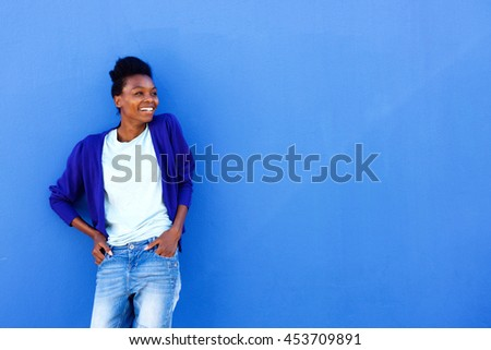 Portrait of happy young african female standing against blue wall with copy space